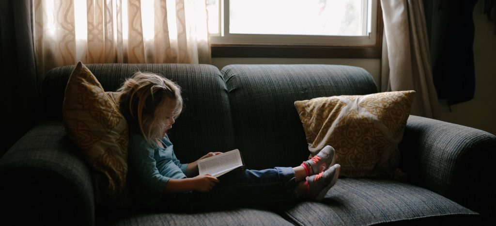 Young girl reads book on couch