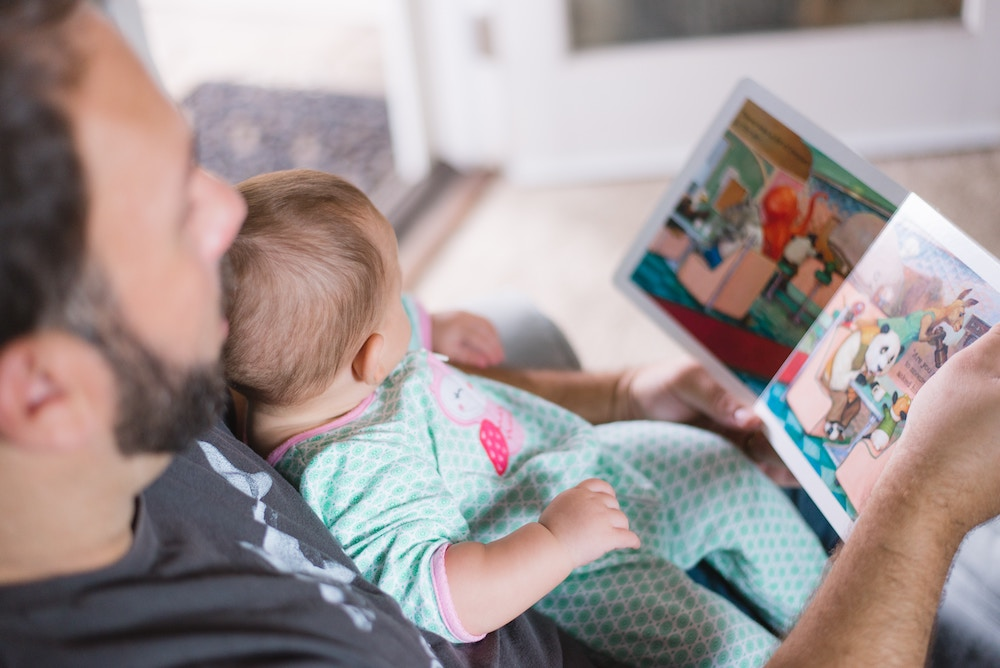 Father reads vibrant picture book to infant in onesie